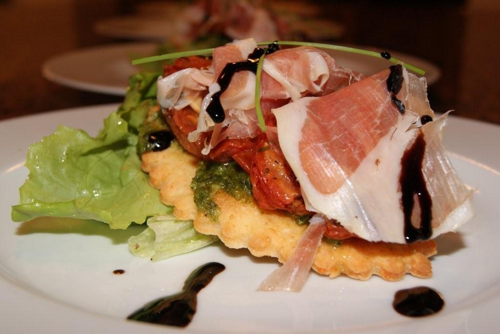 Parmesan tart with roasted tomatoes, pistachio pesto and Parma ham